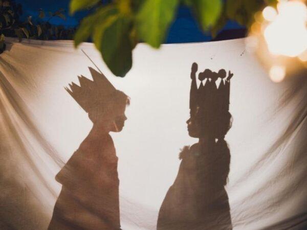 Актёры мальчик и девочка за белой простынью, тени